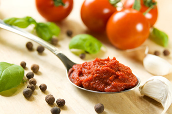 a spoon of tomato paste next to garlic cloves, peppercorns, basil leaves, and tomatoes