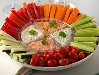 fresh sliced carrots, celery, bell peppers, and zucchini arranged on a platter surrounding small bowls of dip