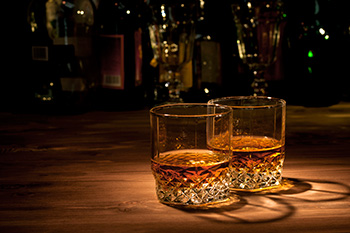 two highball glasses of whiskey on a bar