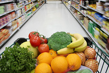 a grocery cart full of fruits and vegetables from the perspective of one pushing the cart