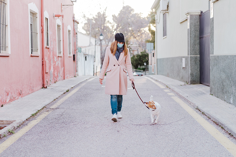 a woman wearing a surgical mask walking her dog