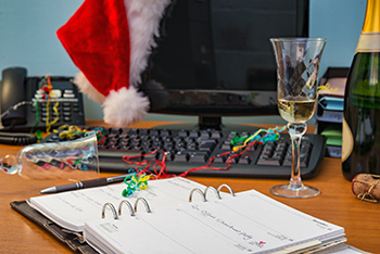 An office desk with computer during a holiday party - with Santa hat and a glass of champagne on the desk
