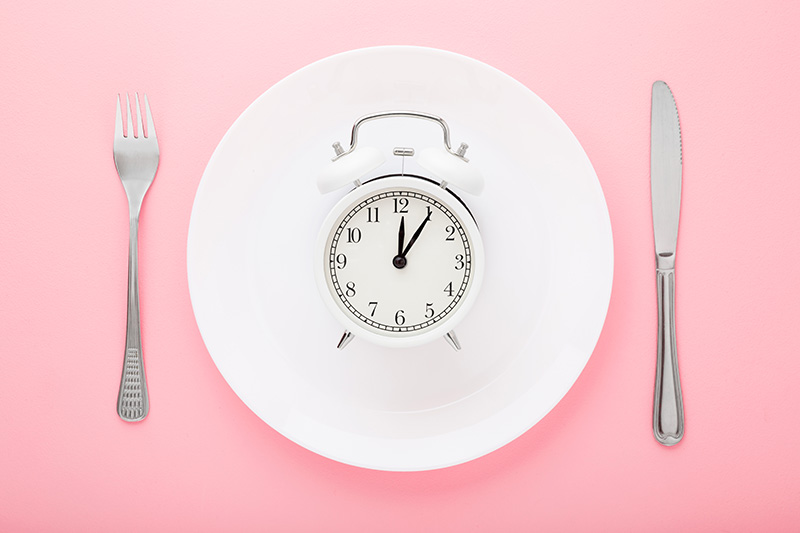 an alarm-style clock set to 12:06 on a plate flanked by a knife and fork