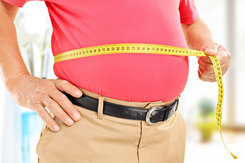 an overweight person measuring their waist with a tape measure